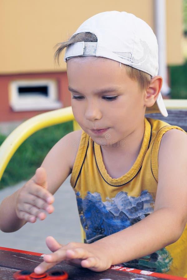Schüler des jungen jugendlich, der populäres Unruhespinnerspielzeug - nahes hohes Porträt hält Glückliches lächelndes Kind, das m stockbilder