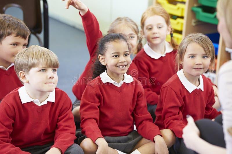 Schüler, die auf Mat Listening To Teacher sitzen lizenzfreie stockfotografie