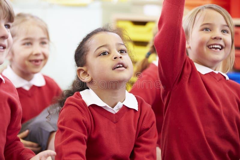 Schüler, die auf Mat Listening To Teacher sitzen stockfotos