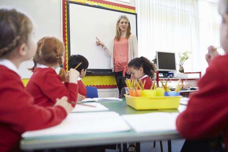Schüler, die bei Tisch als Lehrer Stands By Whiteboard sitzen stockfoto