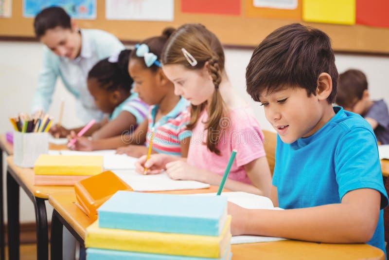 Schüler, die an ihren Schreibtischen in der Klasse arbeiten stockbilder