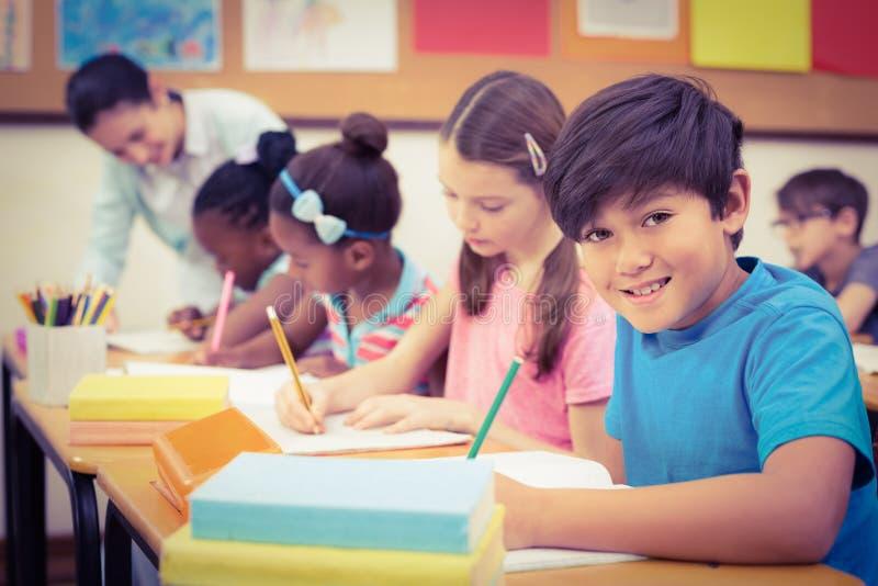 Schüler, die an ihren Schreibtischen in der Klasse arbeiten lizenzfreie stockfotografie