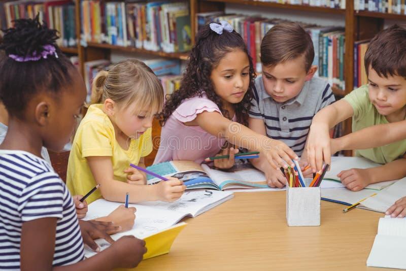 Schüler, die am Schreibtisch in der Bibliothek zusammenarbeiten lizenzfreie stockbilder