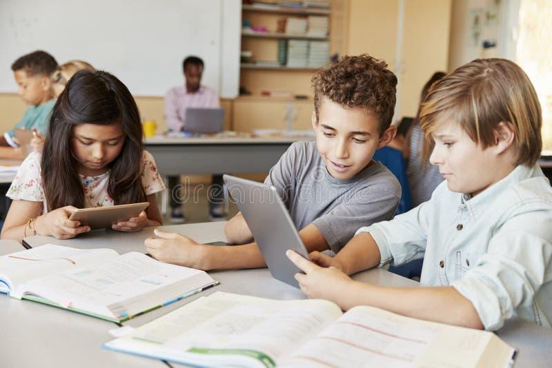 Schüler, die zusammen mit Tablet-Computer in der Klasse arbeiten lizenzfreies stockbild