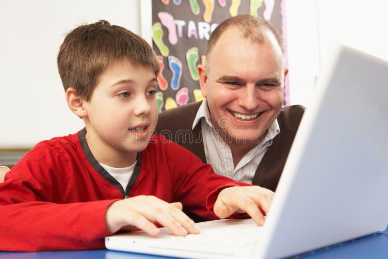 Schüler in IHM Kategorie unter Verwendung des Computers mit Lehrer stockfoto