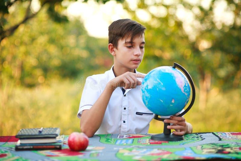 Schüler im Garten zeigt bei Tisch Finger auf Kugel draußen stockfoto