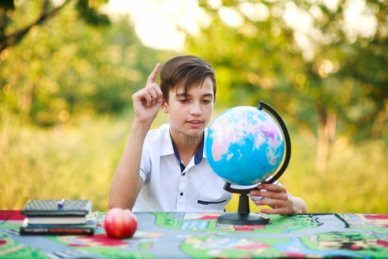 Schüler im Garten zeigt bei Tisch Finger auf Kugel draußen stockbilder