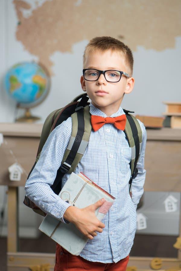 Schüler kleidete in den Gläsern und in einem Rucksack, der im Klassenzimmer steht an stockbilder