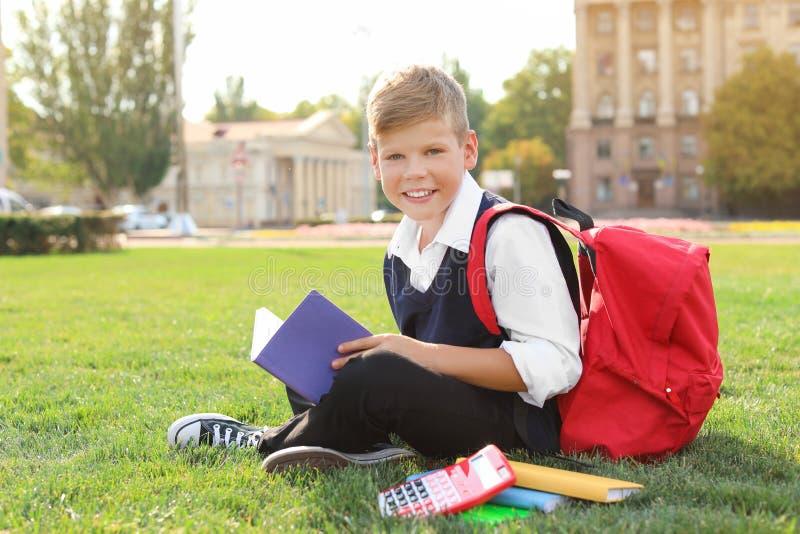 Schüler mit Briefpapiersitzen stockbild