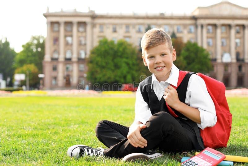 Schüler mit Briefpapiersitzen lizenzfreies stockbild