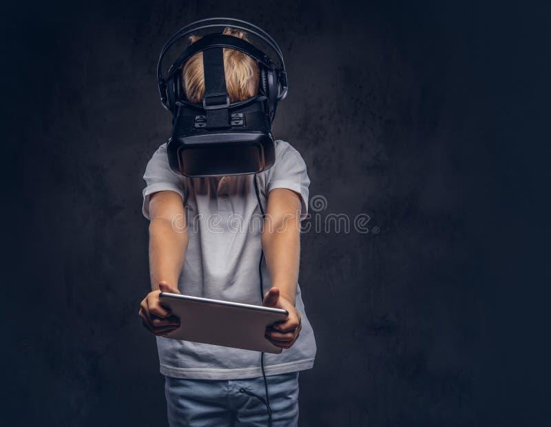 Schüler mit dem blonden Haar kleidete Gläsern einer weißes T-Shirt in tragenden virtuellen Realität und in der Anwendung einer di stockbild