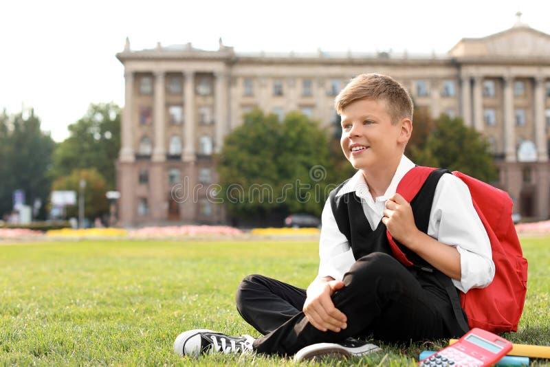 Schüler mit dem Briefpapier, das auf Gras sitzt stockbilder