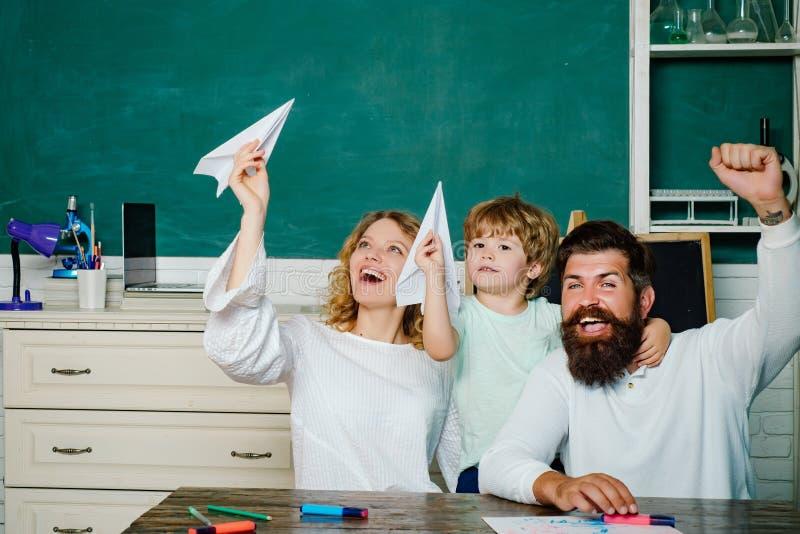 Schüler mit dem Papierflugzeug, das mit Eltern spielt Junge Paare, die seinem Sohn helfen, Hausarbeit zu machen Elternteil, das K stockfotos