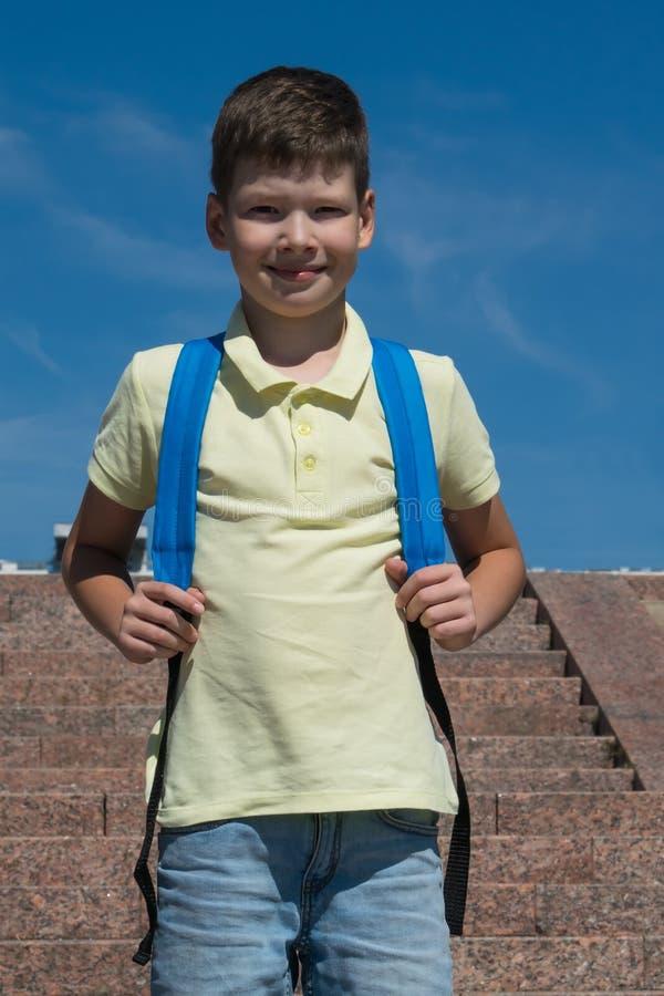 Schüler mit einem blauen Rucksack gegen den Hintergrund eines Treppenhauses zur Schule lizenzfreies stockbild