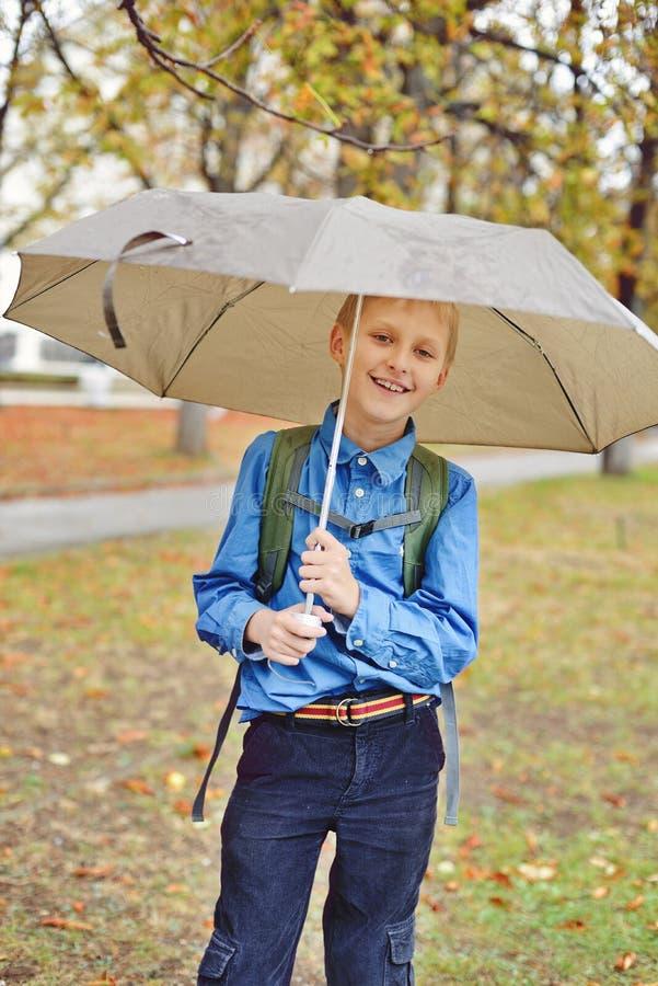Schüler mit Regenschirm stockfotografie