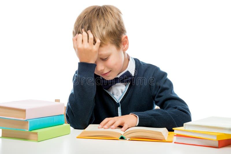 Schüler am Tisch ein Buch, schießend auf einem Weiß lesend stockfoto