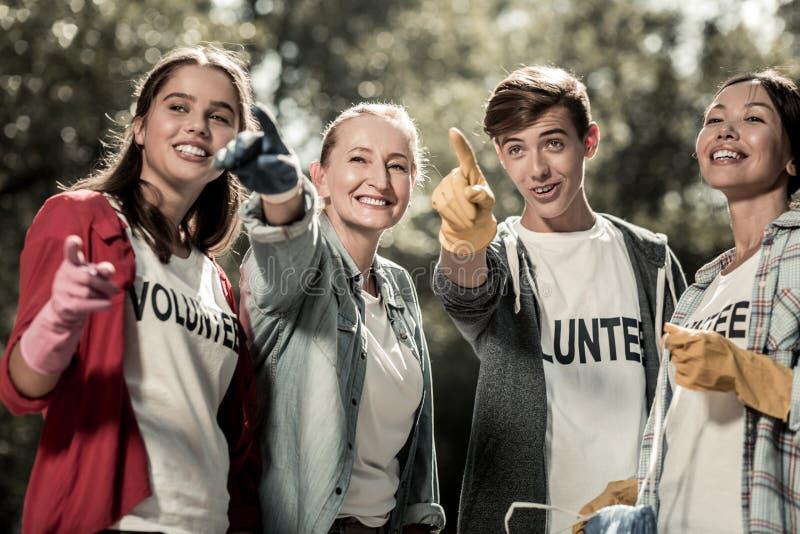 Schüler und ihr Lehrer glaubender Active beim im Wald zusammen sich freiwillig erbieten lizenzfreie stockfotografie