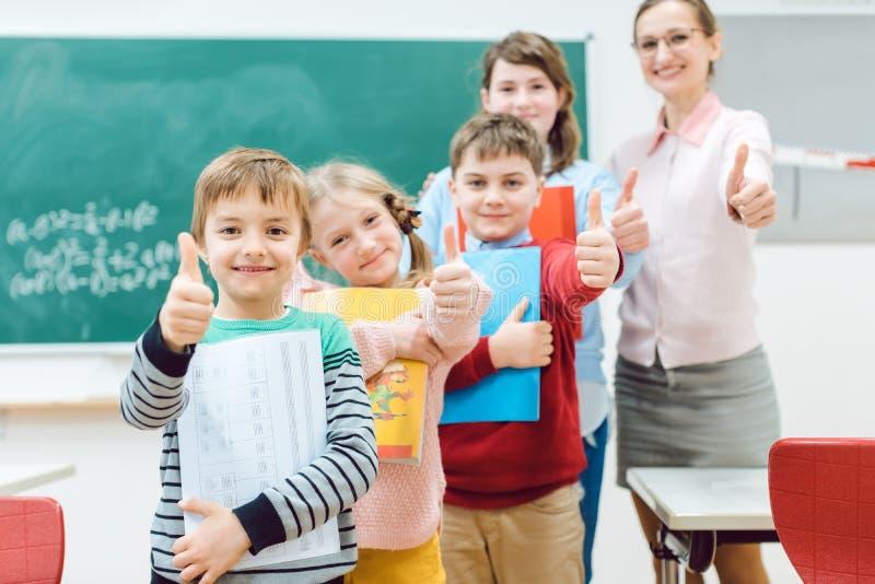 Schüler und Lehrer, die Daumen-oben in der Schule hat Spaß zeigt lizenzfreies stockfoto