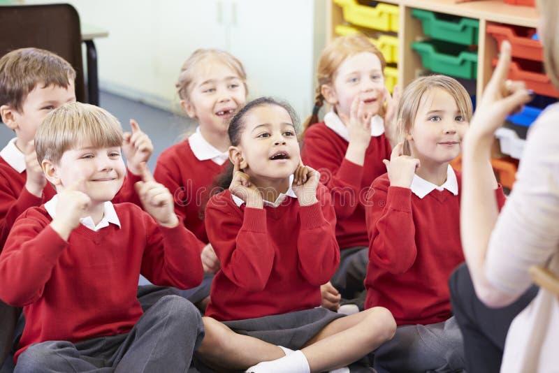 Schüler, welche die Aktionen des Lehrers kopieren, während, Lied singend stockfotografie