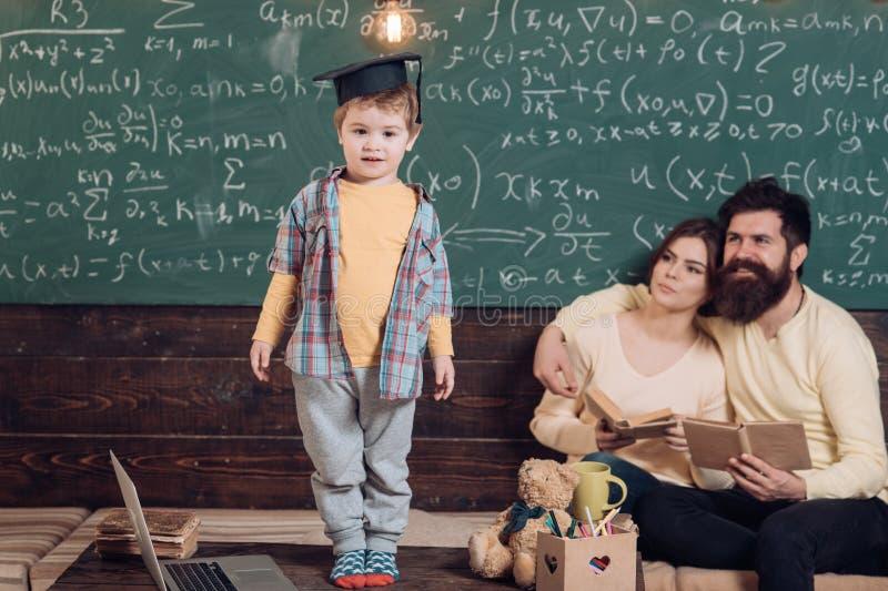 Schülerdurchlaufprüfung Kleiner Schüler in der Staffelungskappe Schüler und Familie in der Schulklasse Ein guter Schüler hat ein  stockbilder