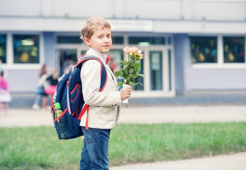 Schülerjunge mit Blumen auf dem Anfang des neuen Schuljahres stockbilder