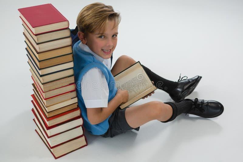Schülerlesebuch beim Sitzen gegen Buchstapel auf weißem Hintergrund stockfoto