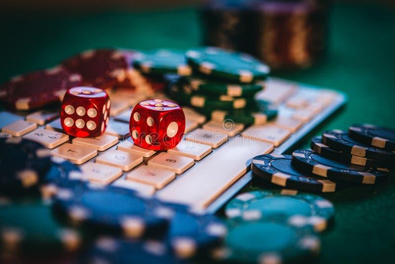 Schürhakenon-line-Sucht Einige Pokerchips und ein paar Rot würfelt auf einer Tastatur Wetten auf Internet-Konzept stockfoto