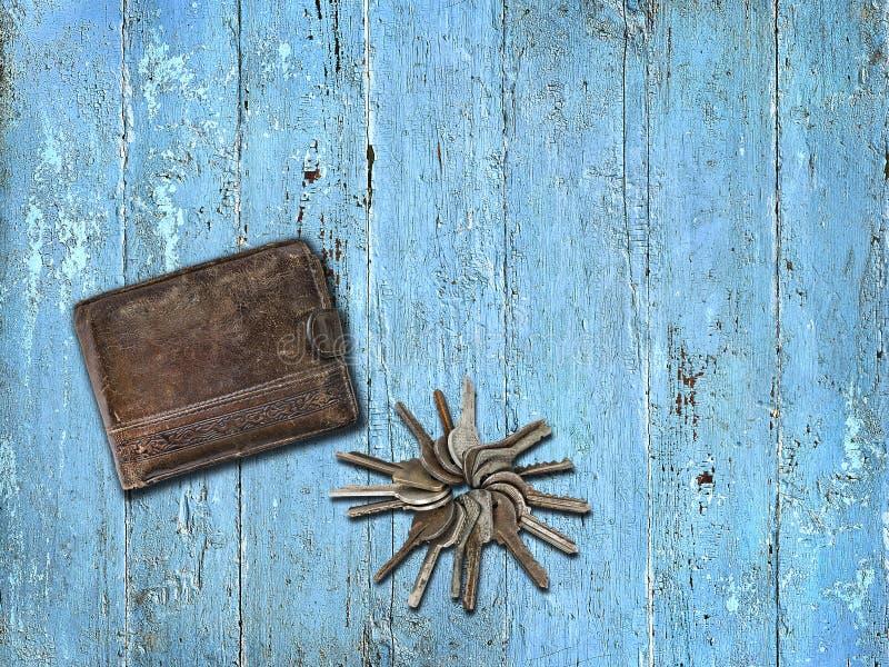 Schürzen Sie und ein Schlüsselbund auf einem blauen hölzernen Hintergrund stockfoto