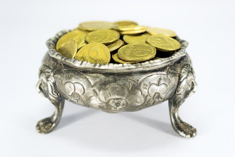 Schüssel auf drei Löwefuß mit Münzen stockfotografie