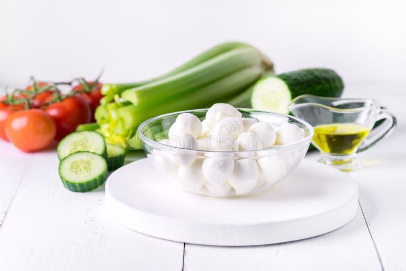 Schüssel Bocconcini-Mozzarella-neuer Tomaten-Gurken-Sellerie-Olive Oil Italian Salad Healthy-Lebensmittel-Weiß-Hintergrund stockfotos