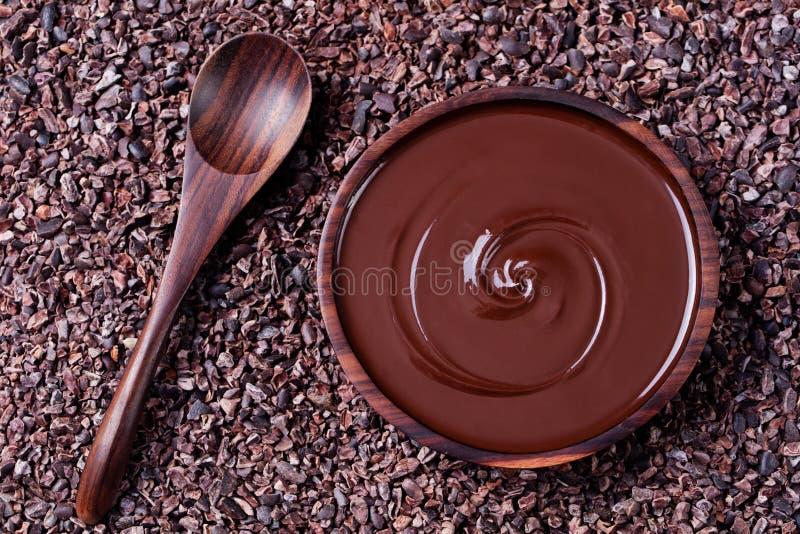 Schüssel der geschmolzenen Schokolade und des hölzernen Löffels auf zerquetschten rohen Kakaobohnen, Spitzenhintergrund Kopieren  stockfoto