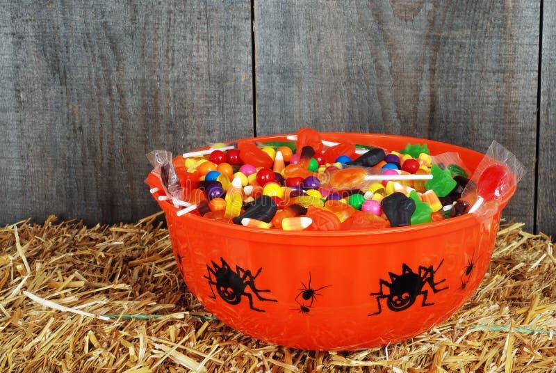 Schüssel der Halloween-Süßigkeit auf Stroh stockfotos