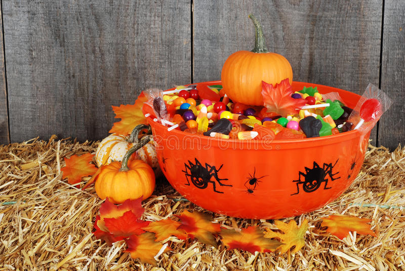 Schüssel der Halloween-Süßigkeit mit Fallblättern stockbilder