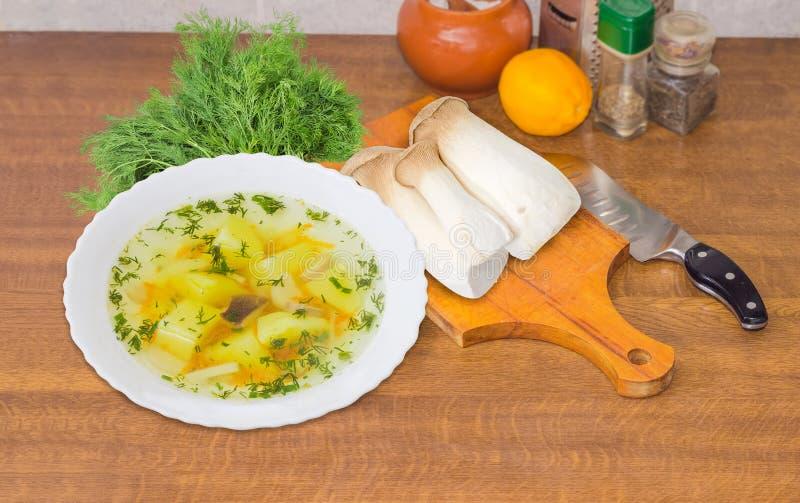 Schüssel der Pilzsuppe und des ungekochten Eringi vermehrt sich dazu explosionsartig lizenzfreies stockbild