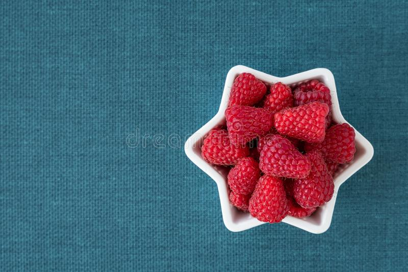 Schüssel frische rote Himbeeren zum Nachtisch, weiße sternförmige keramische Schüssel, blauer Gewebehintergrund lizenzfreie stockfotos