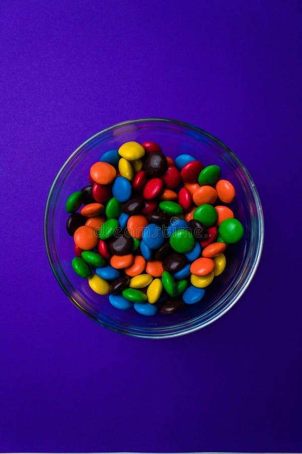 Schüssel gefüllt mit mehrfarbiger Süßigkeit auf einem purpurroten Hintergrund stockfotografie