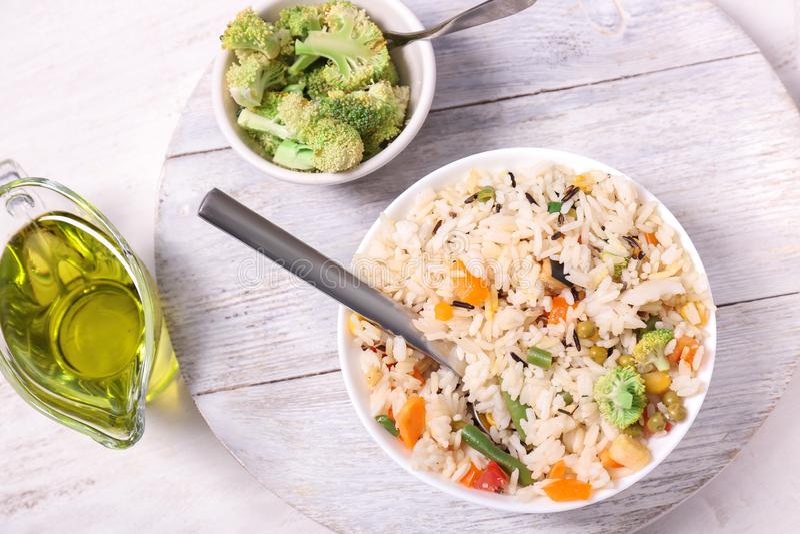 Schüssel geschmackvoller Reis mit Gemüse, Olivenöl und Brokkoli auf weißem Holztisch lizenzfreie stockbilder