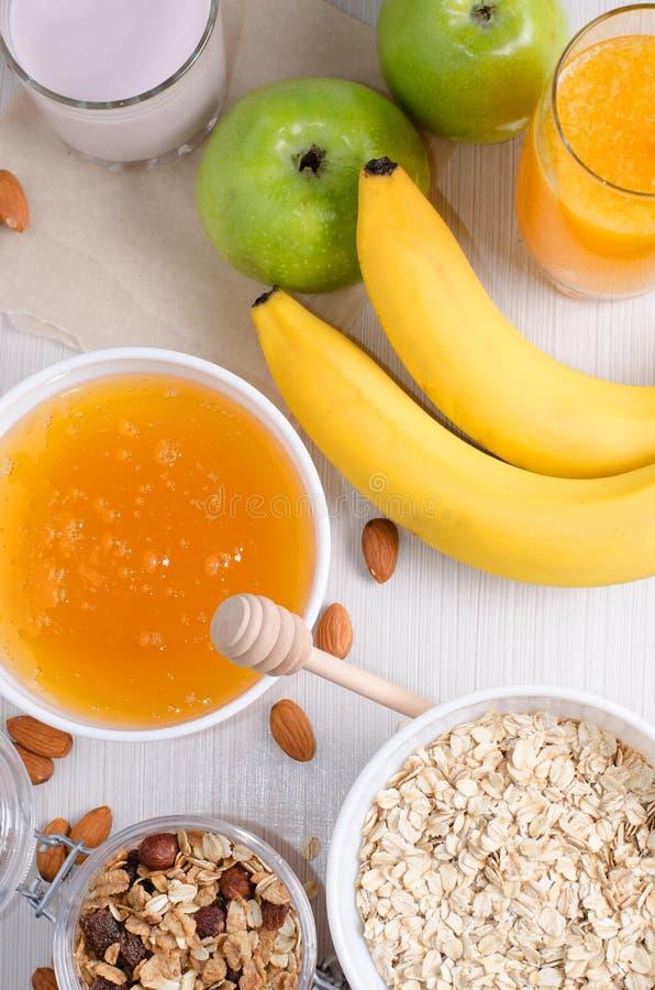 Schüssel Hafermehl und Rosinen Honig, Bananen, grüne Äpfel, Nüsse stockfoto