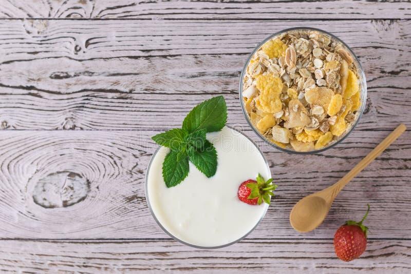 Schüssel Jogurt und Schüssel des Hafermehls mit hölzernem Löffel auf Holztisch Flache Lage stockbild
