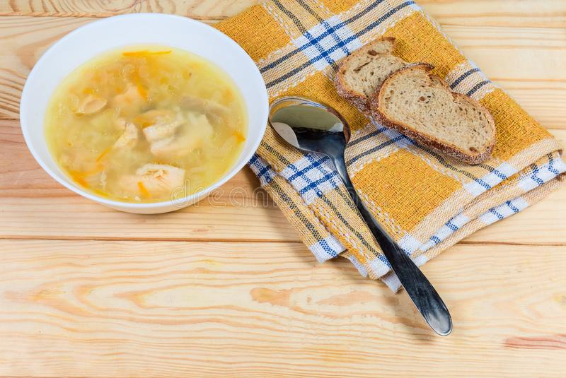 Schüssel klare Lachssuppe, Löffel, Brot auf rustikaler Tabelle stockfotografie