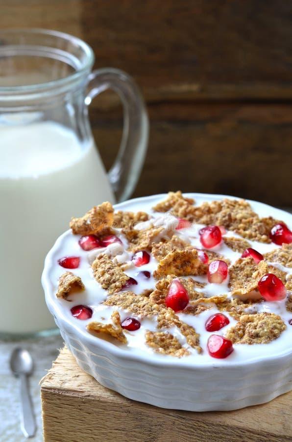 Schüssel Milch mit Getreide und Granatapfelsamen stockfotografie
