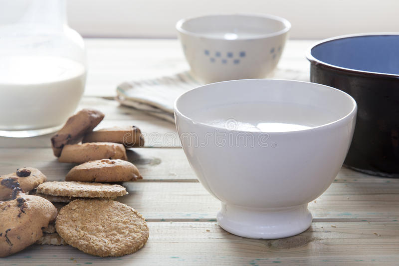 Schüssel Milch mit Keksen und einer zu erhitzen Kasserolle lizenzfreies stockfoto