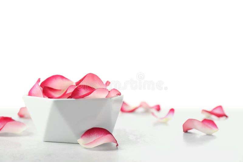 Sch?ssel mit den rosafarbenen Blumenbl?ttern auf Tabelle gegen wei?en Hintergrund stockfotografie