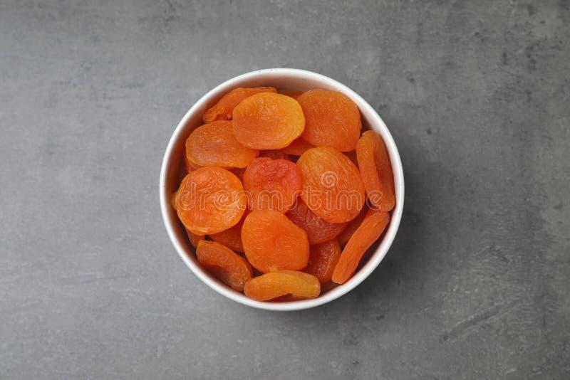 Schüssel mit getrockneten Aprikosen auf grauem Hintergrund, Draufsicht stockbilder