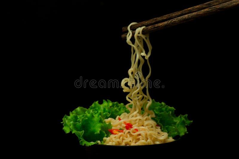 Schüssel Nudeln mit dem Gemüse, das auf schwarzer, getrockneter chinesischer Nudel mit knusperigem gebratenem Schweinefleisch lok lizenzfreies stockfoto