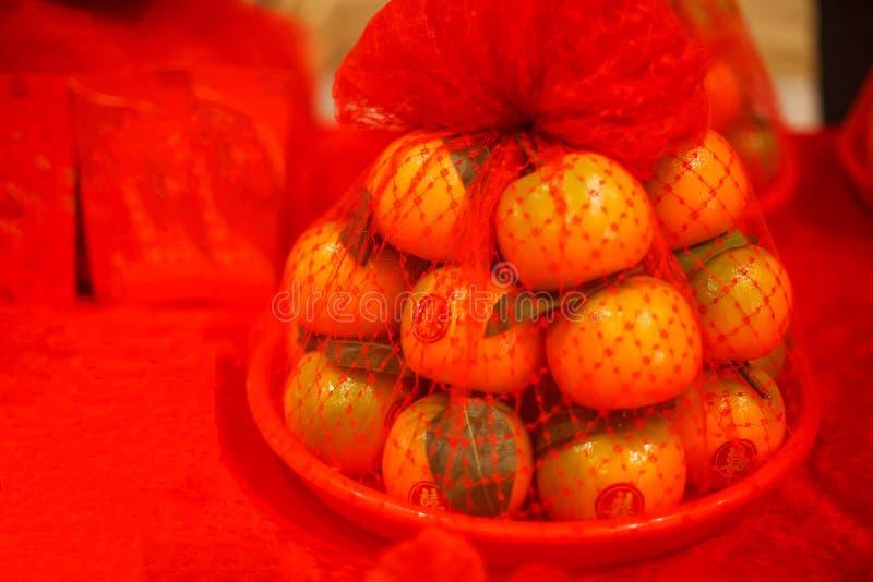 Schüssel Orangen mit roten Aufklebern in Wortbedeutung Glück des chinesischen Schriftzeichens unter Verwendung als Geschenk für c lizenzfreie stockfotos