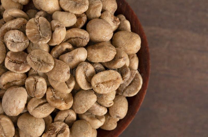 Schüssel rohe Rohkaffee-Bohnen auf einem Holztisch stockfotografie
