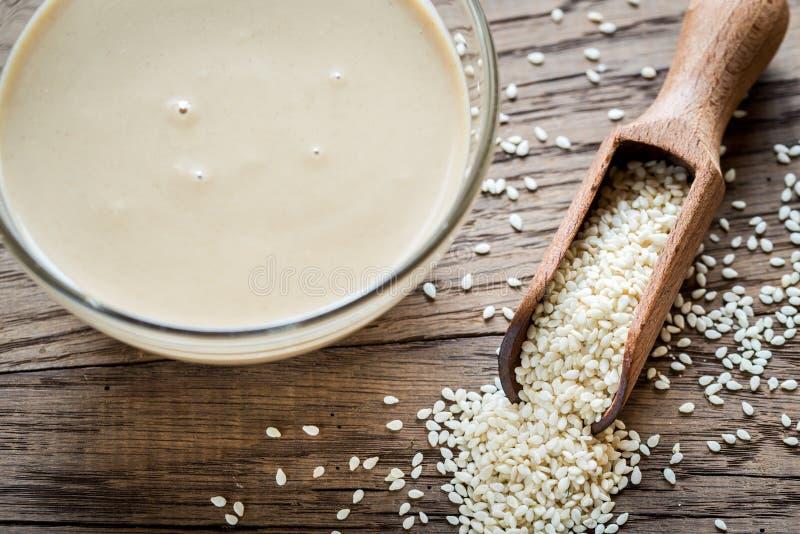 Schüssel tahini mit Samen des indischen Sesams stockbilder