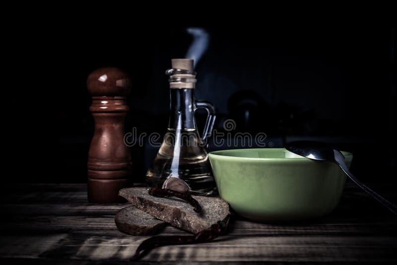 Schüssel und Löffel, Brot und Gewürze auf gebranntem Holztisch Vorbereiten für traditionelles ländliches Abendessen getont lizenzfreie stockbilder
