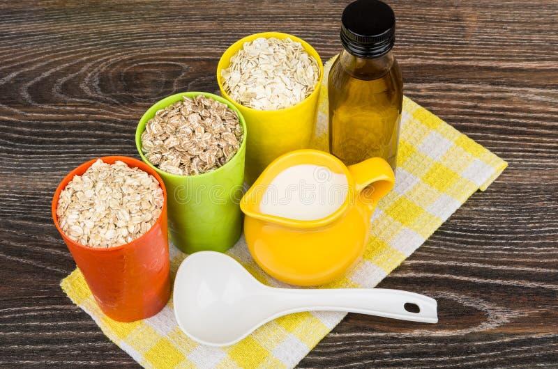 Schüssel und Schalen mit Hafer, Roggen, Gerstenflocken, Pflanzenöl stockfotos